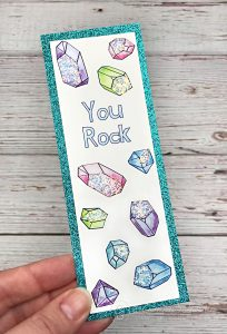 Crystal patterned glittered bookmark held in front of white wood background.