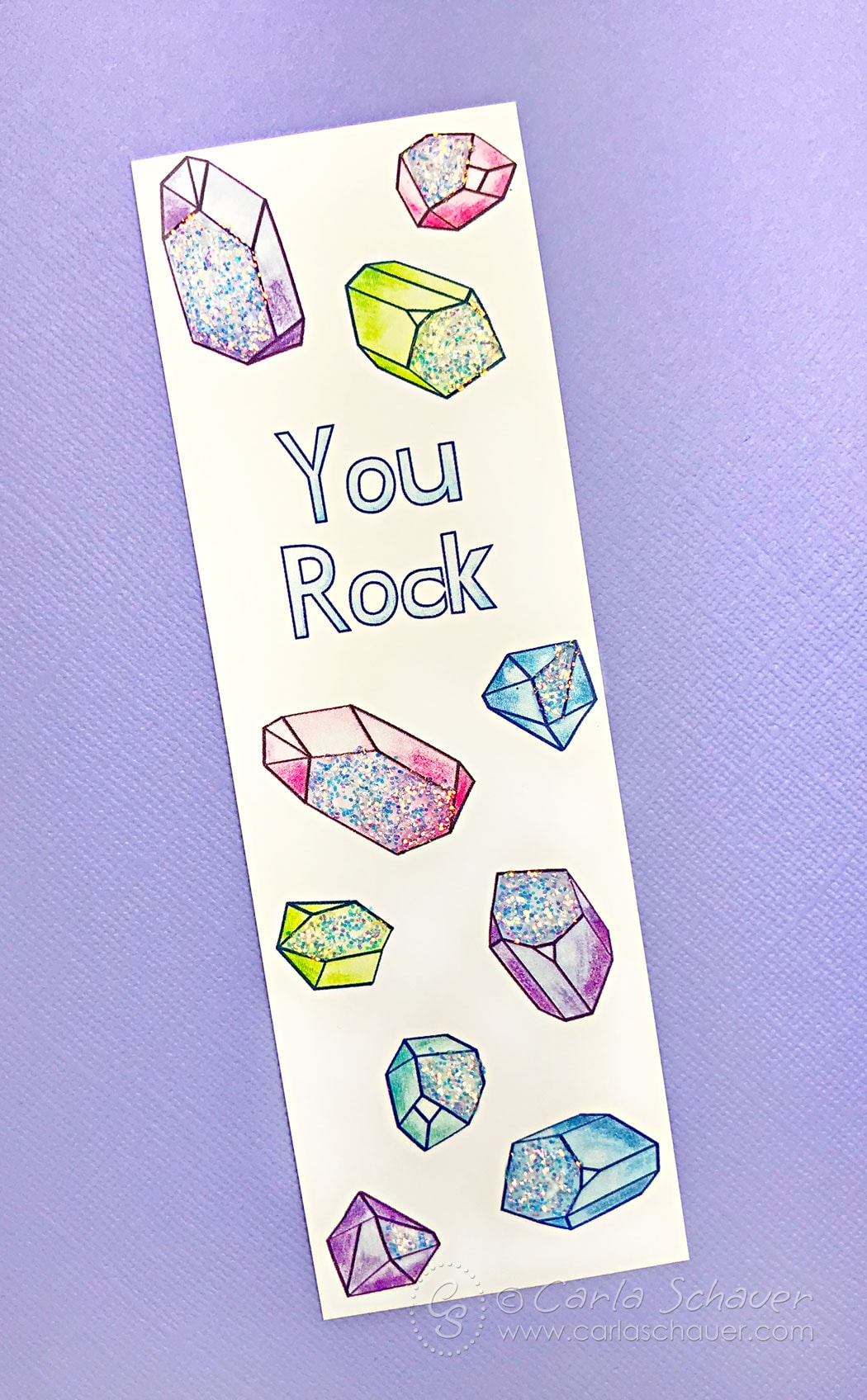 Glittered crystal patterned bookmark on purple background