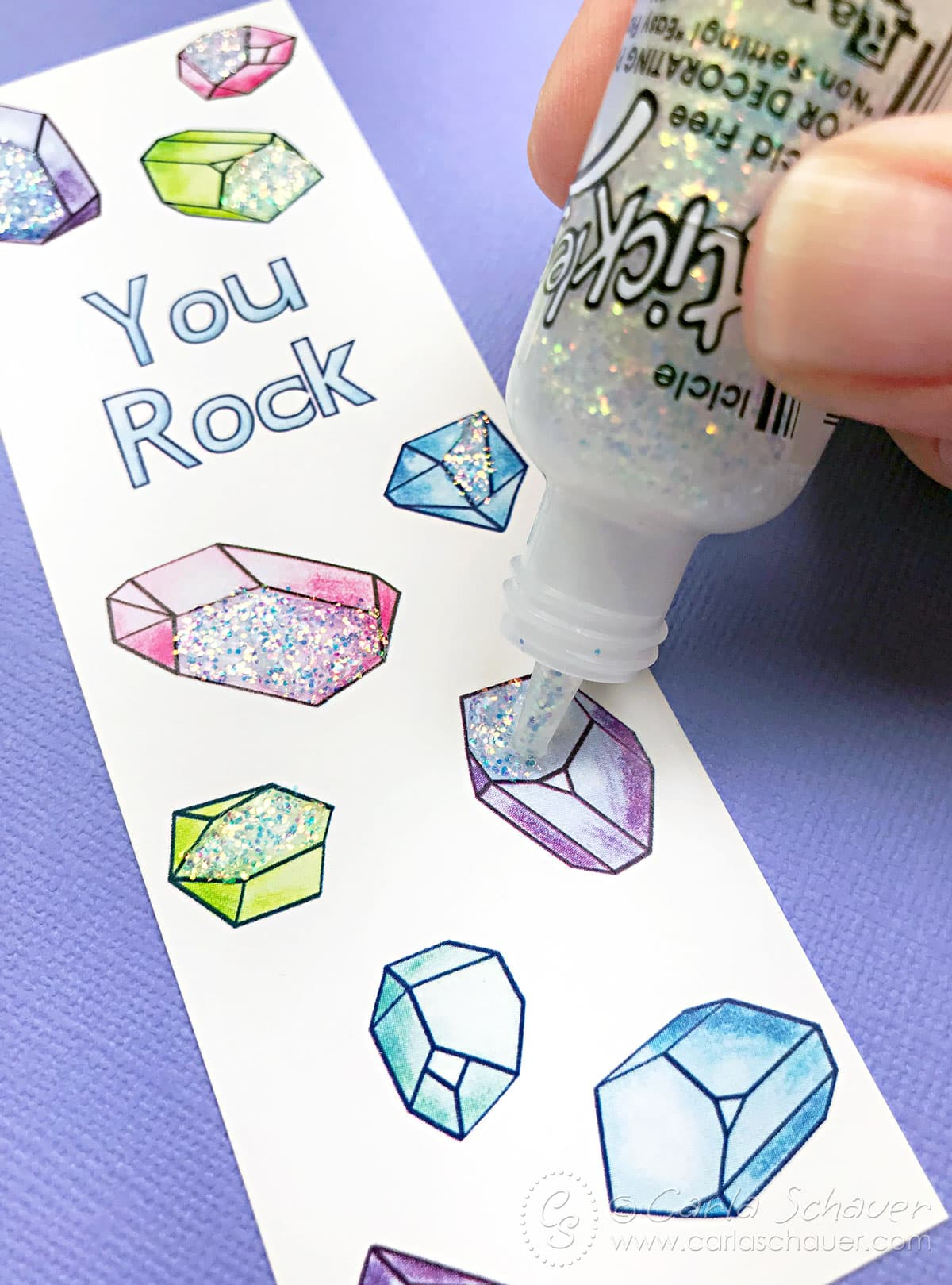 Adding glitter glue to crystal patterned bookmark.