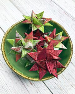Green bowl filled with folded Froebel Star ornaments on wood table.