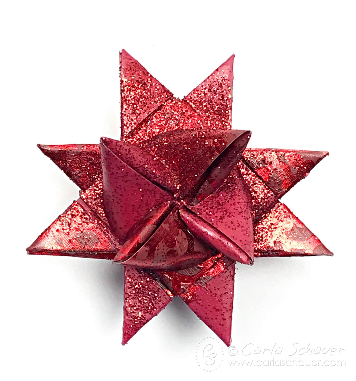 Red Wax Dipped and Glittered Froebel Star Ornamenton white background