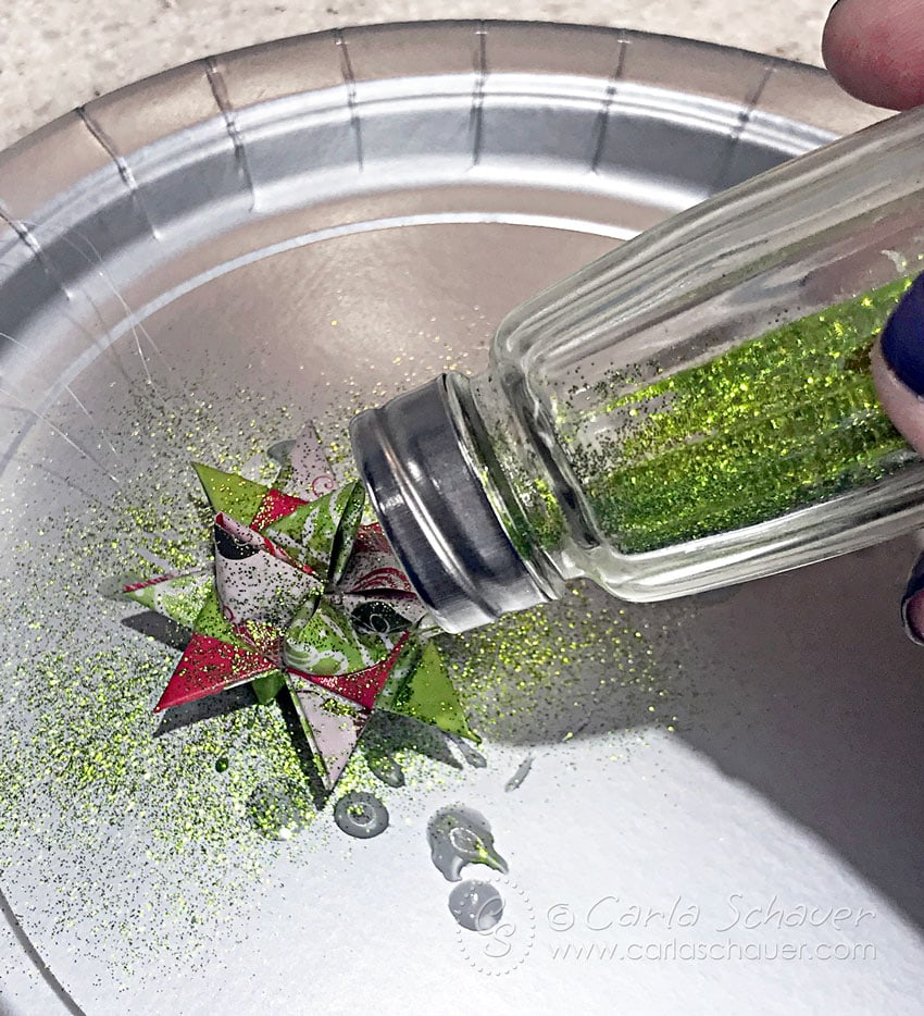 Shaking green glitter onto german star ornament dipped in wax.