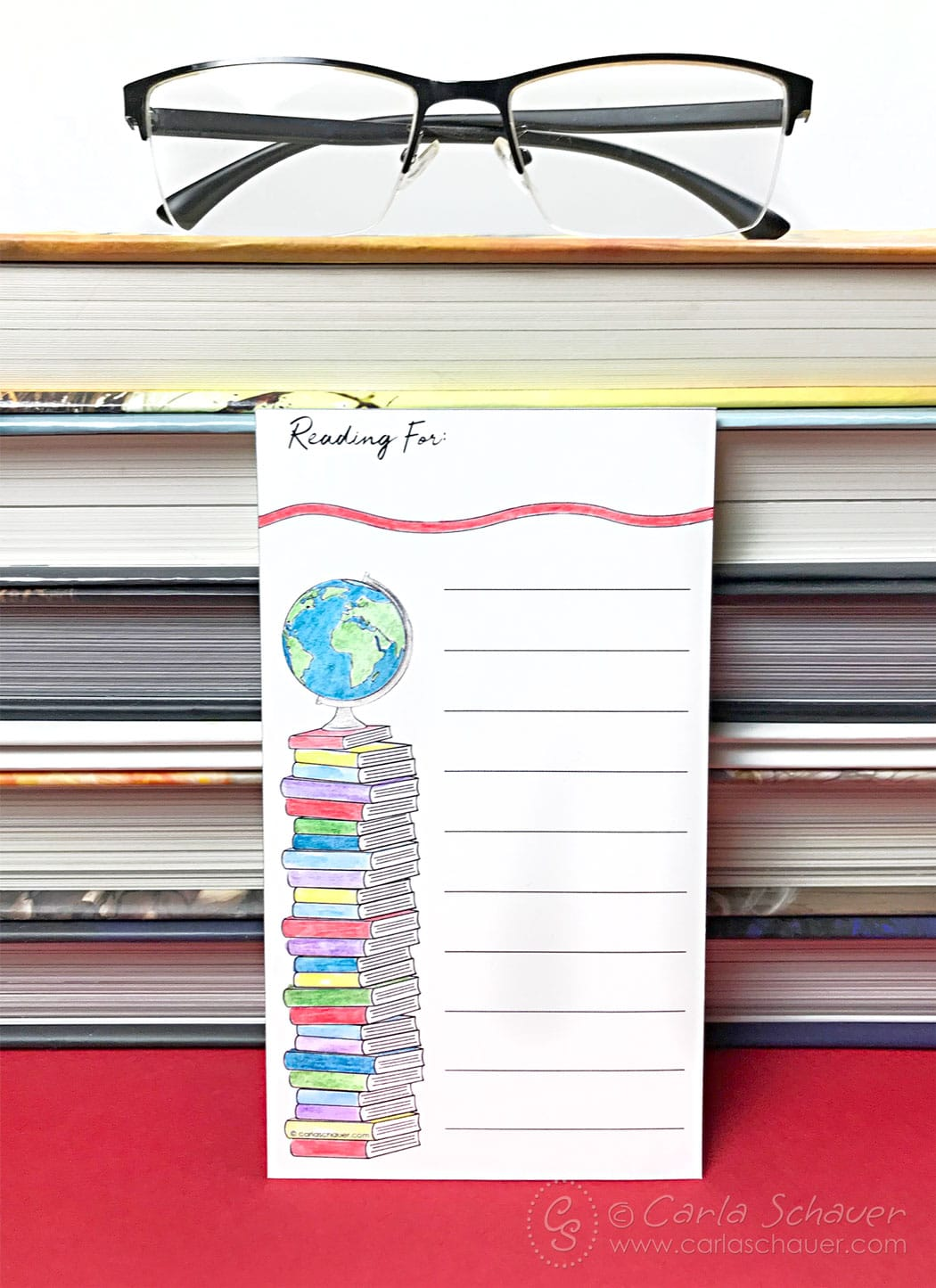 Printable readiing log propped against stack of books.