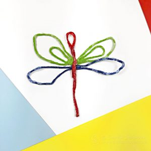 Waxed string dragonfly on colored paper.