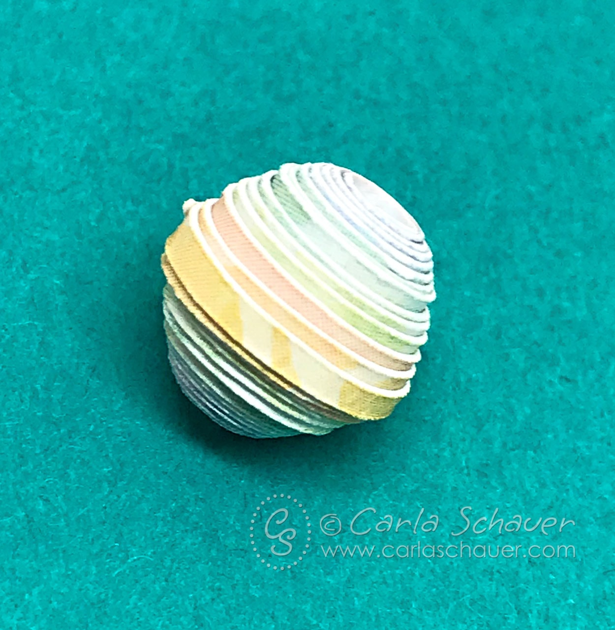 Rainbow rolled paper bead on turquoise backround.