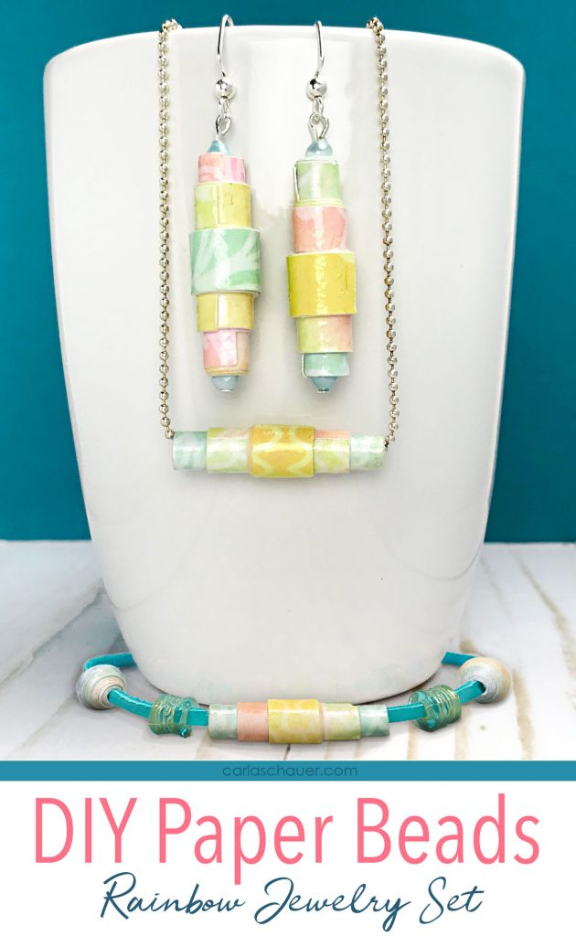 Paper bead earrings, necklace, and bracelet set on white mug.