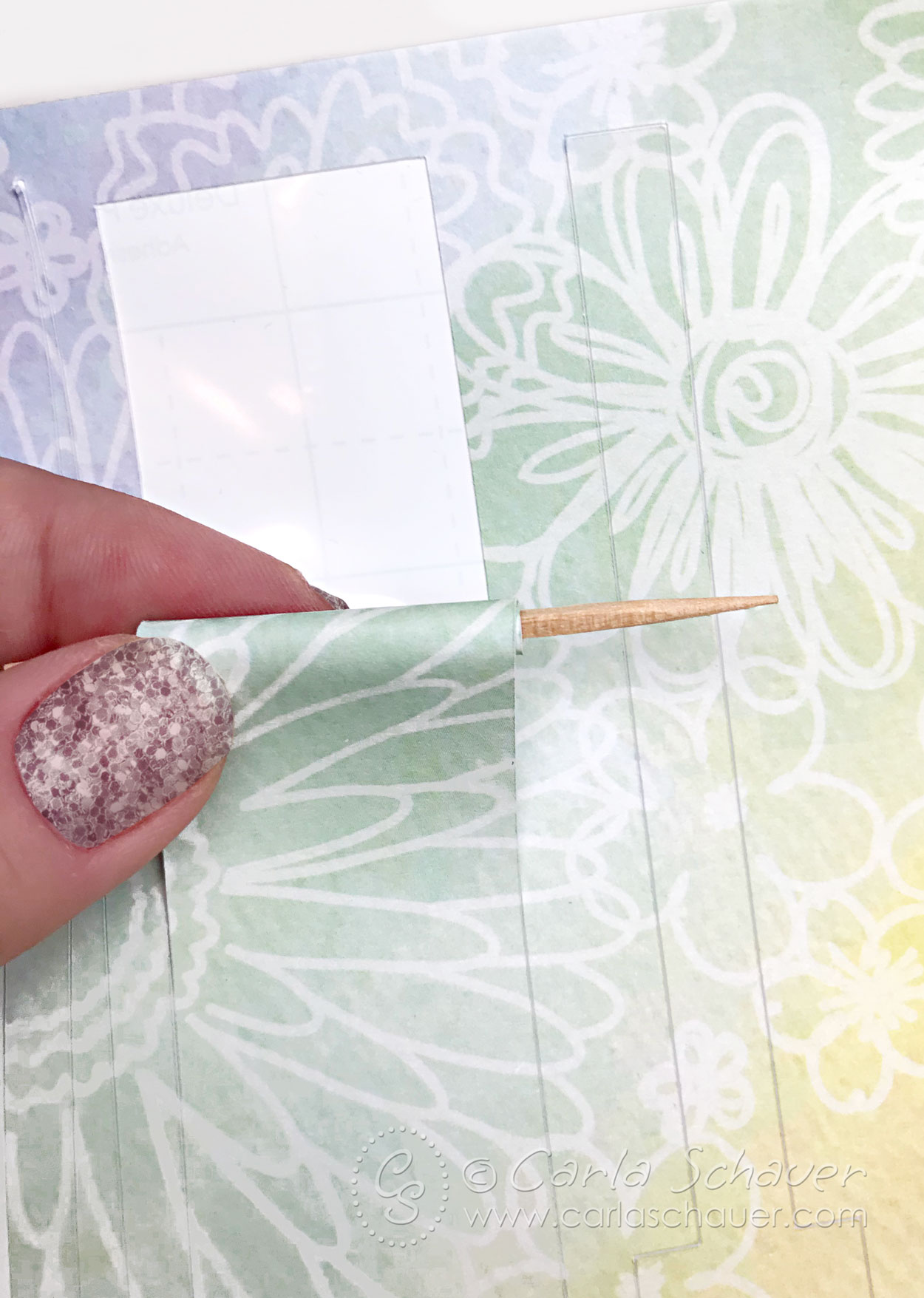 Paper being rolled around toothpick to make bead