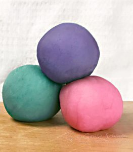 3 balls of multicolored homemade playdough.