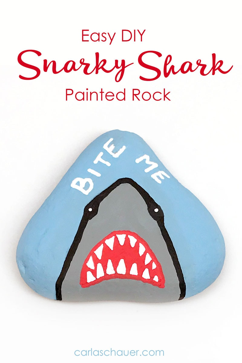 "Snarky Shark Painted Rock on white background with ""bite me"" phrase."