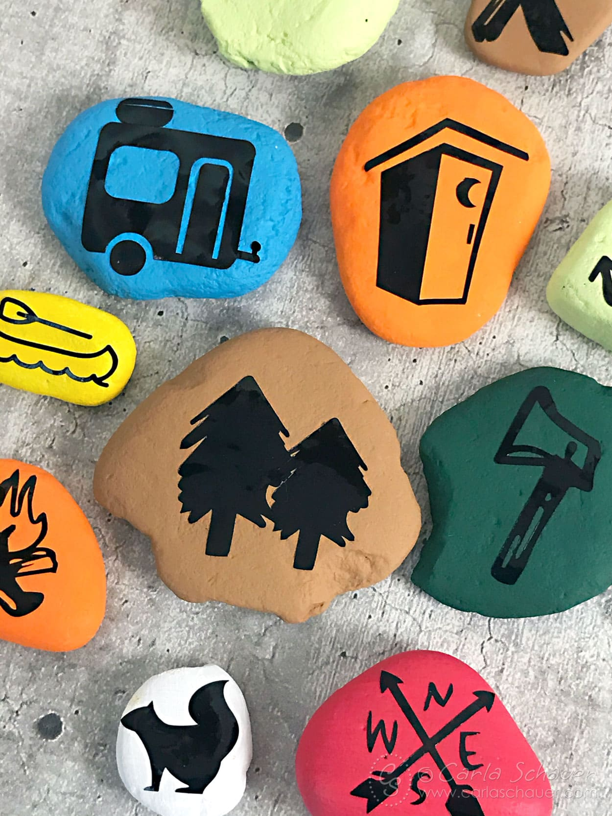Close up of painted stones with camping icons.