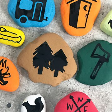 Closeup photo of painted rock stones with camping icons.