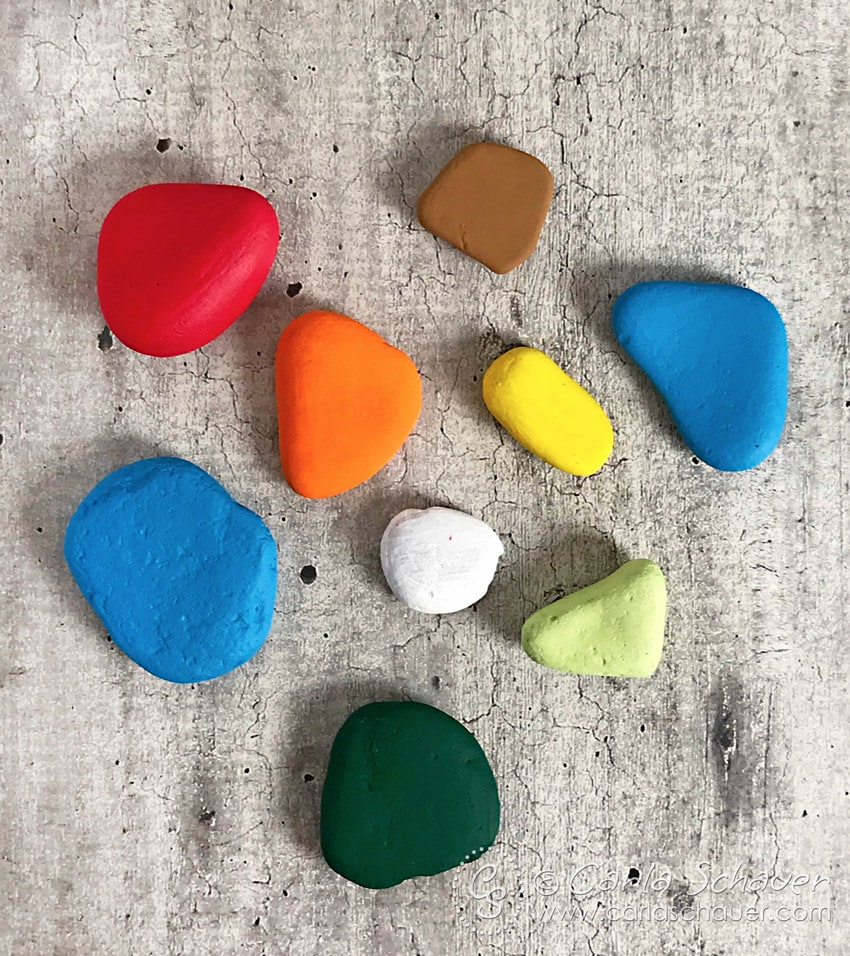 Colorful painted rocks on cement background.