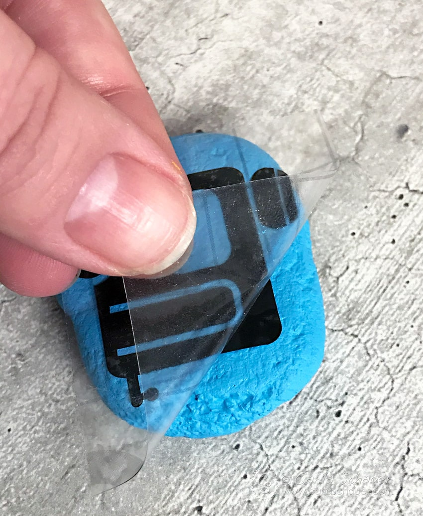 Vinyl camper icon being applied to blue rock.