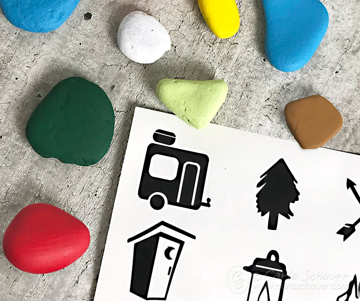 Black vinyl camping icons and colorful painted rocks.
