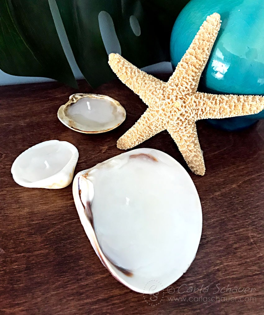 DIY Candles in seashells on wood table with starfish.