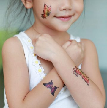 Child wearing 3 temporary tattoos.