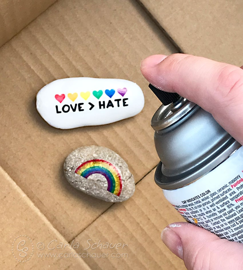 Acrylic sealer being sprayed on pride-themed decorated rocks.