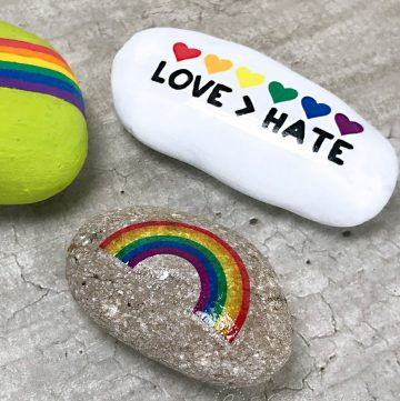 LGBTQ+ Pride craft painted rocks using temporary tattoos on cement background.