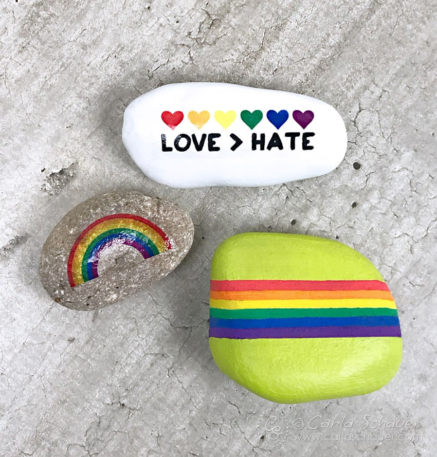 Pride rainbow painted rocks on cement background.