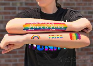Pride Rainbow Tattoos on crossed arms