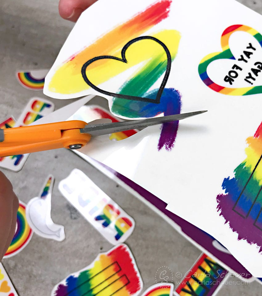 Cutting out a rainbow heart from tattoo paper.