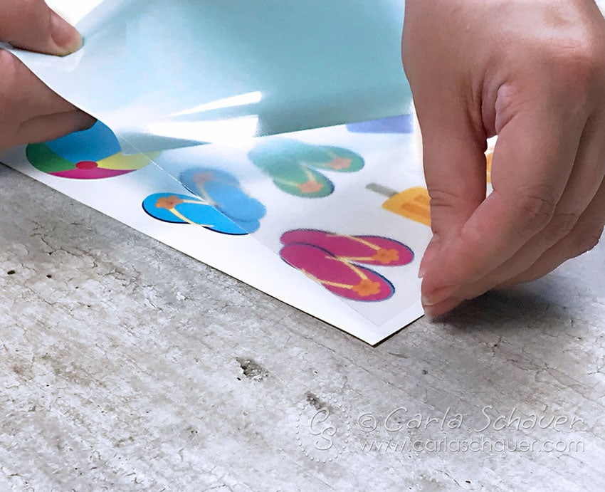 Applying adhesive sheet to printed temporary tattoo images.