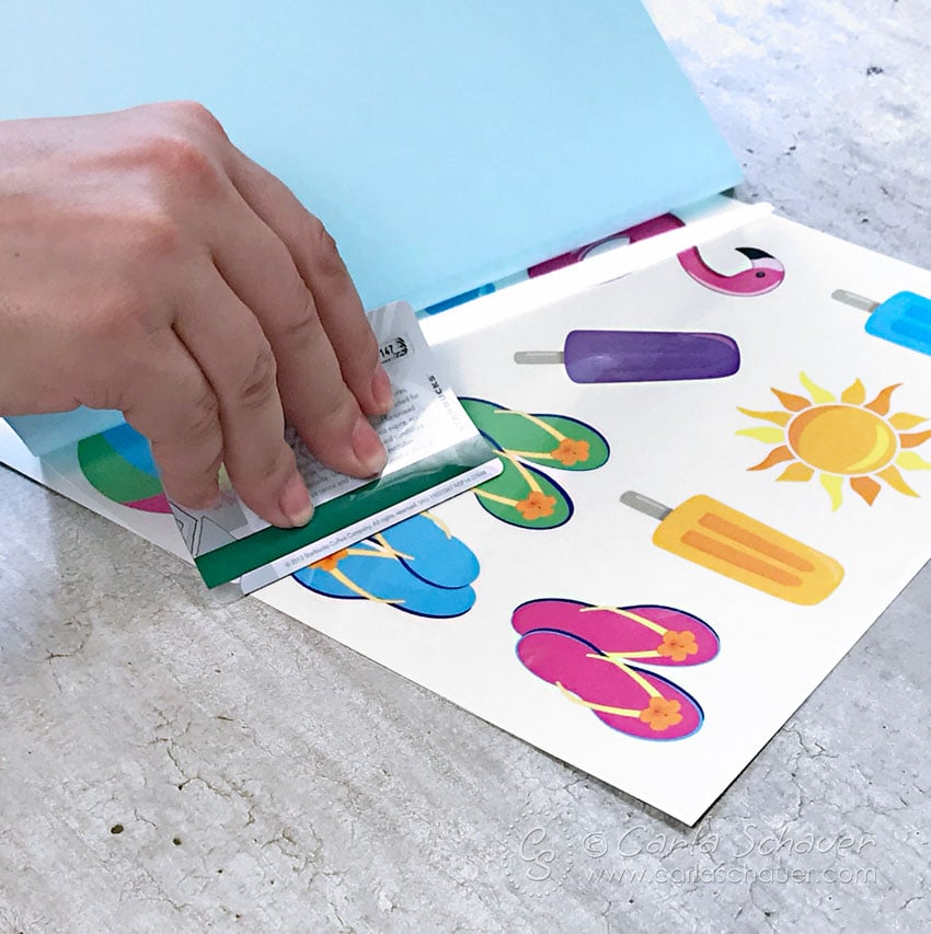 Smoothing adhesive onto printable temporary tattoos with gift card edge.