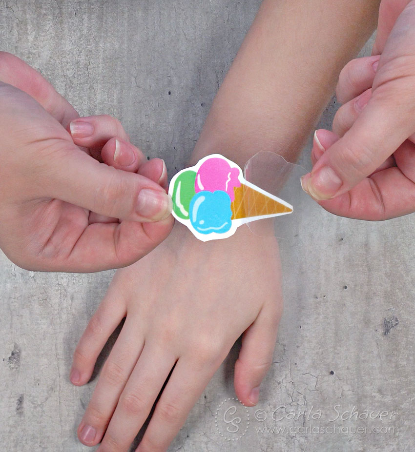 Peeling clear backing from ice cream cone temporary tattoo
