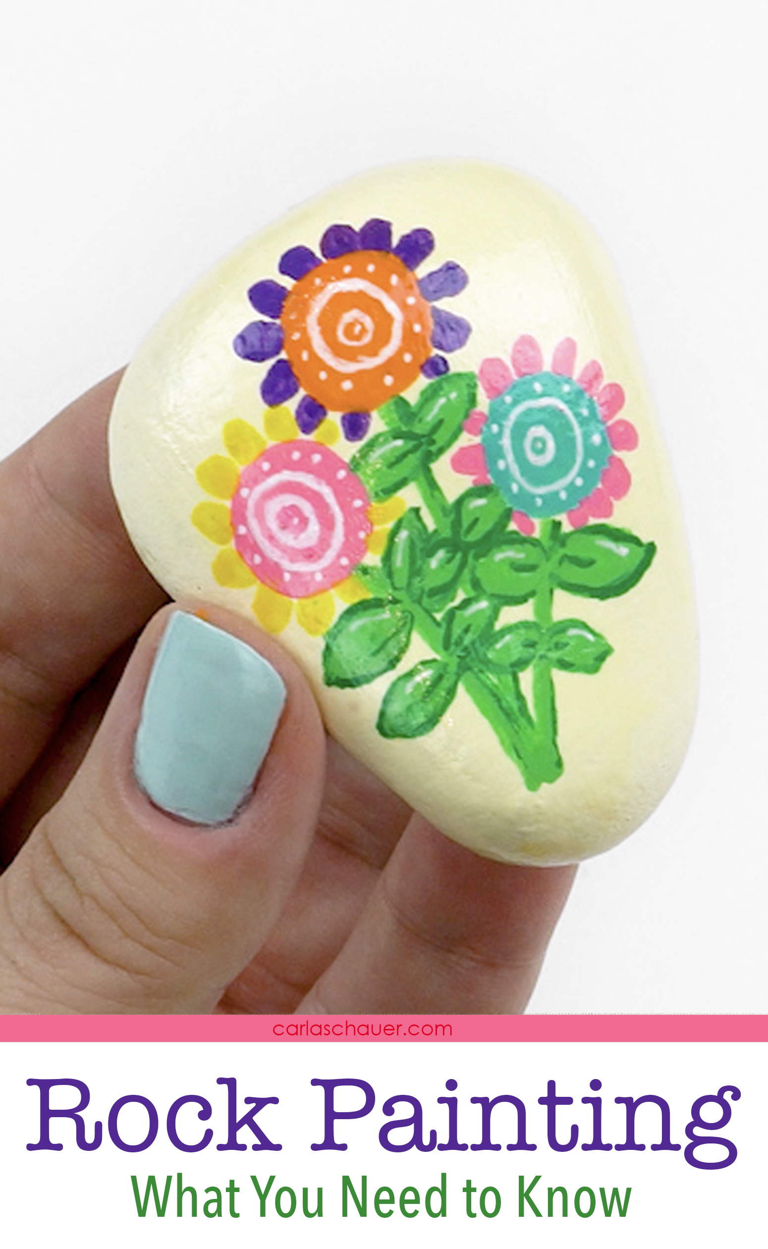 Hand holding cream painted rock with colorful flower design.