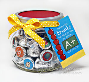 Jar of chocolate kisses decorated with school themed printable circles, with red lid, yellow ribbon, and printable tag.