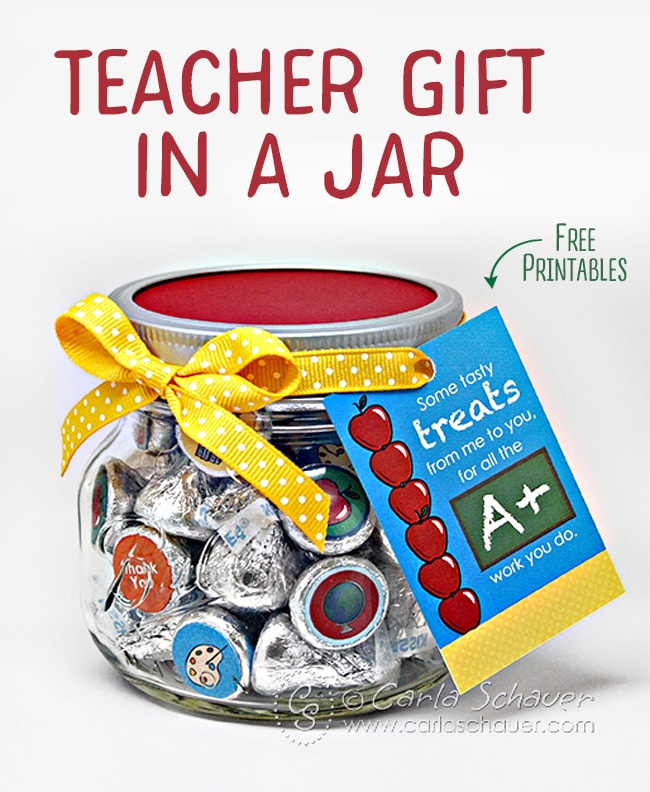 "Jar of chocolate kisses decorated with school themed printable circles, with red lid, yellow ribbon, and printable tag. Text ovelay that reads ""Teacher Gift in a Jar""."
