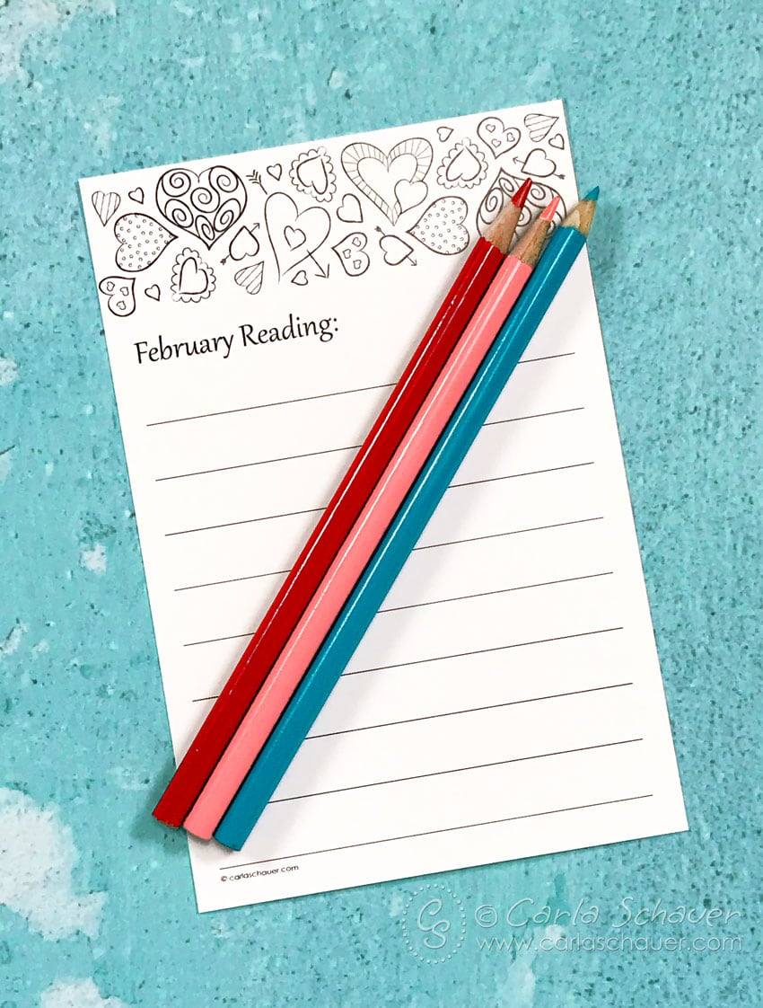 Red, pink, and teal colored pencils lying on top of black & white printed book log with heart border.
