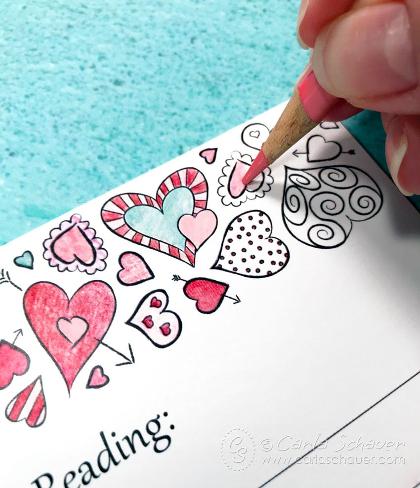 Hand coloring in hearts using a pink colored pencil on a printable Valentine coloring page.