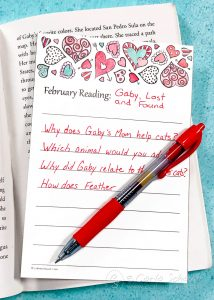 Book log with heart border and red pen, on open book on teal background.