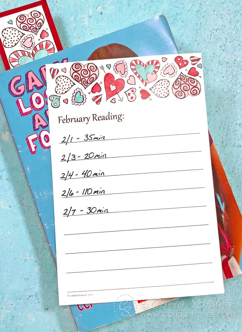 Printable Valentine Reading Log lying on closed book with bookmark inside, on teal background.