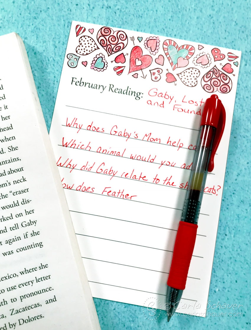 Book log with heart border and red pen, next to open book on teal background.