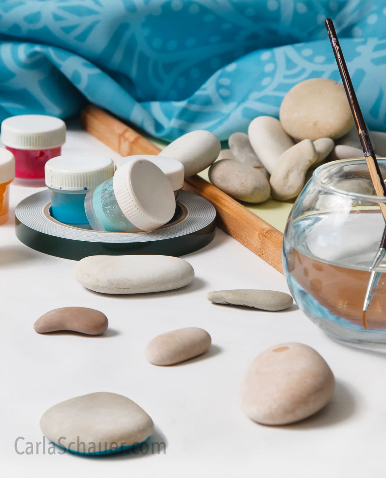 Smooth rocks, paint jars, and fishbowl with paintbrushes in water. Rock painting scene with teal fabric background.