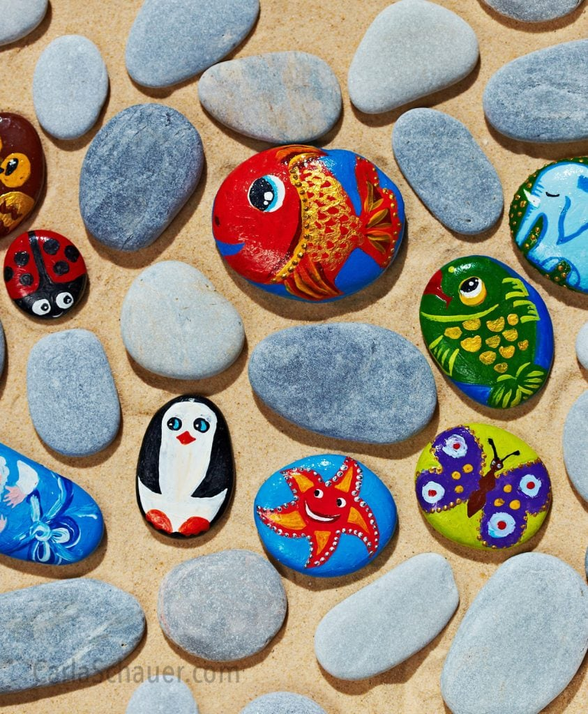 A mix of animal-painted and unpainted flat stones.