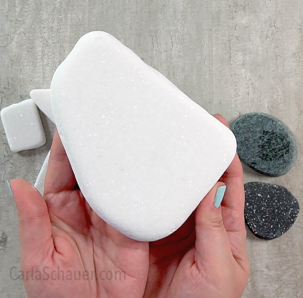 Hands holding large white Santorini Stone for painting.