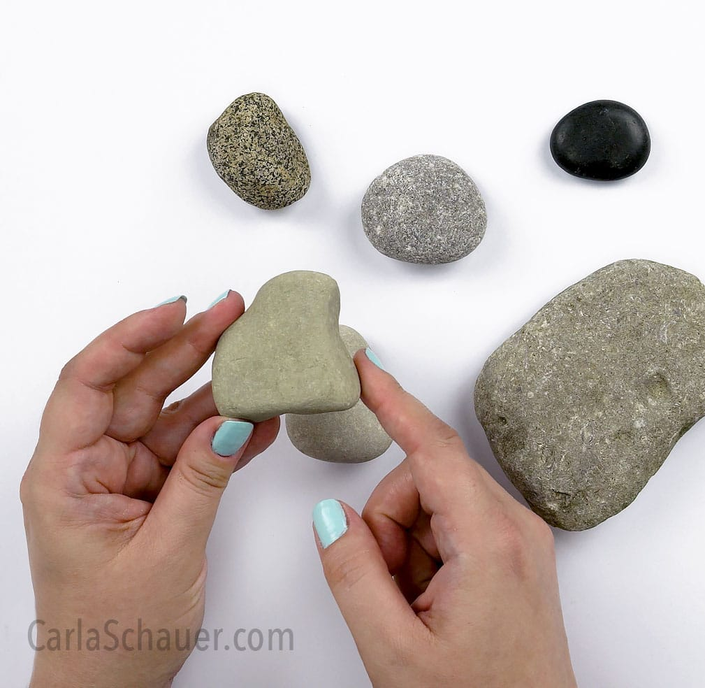 Hands holding a triangle shaped rock, with other rocks in background on white table.